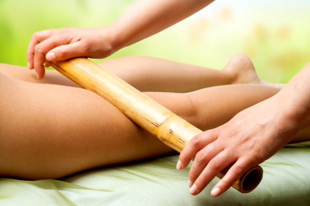 Close up of therapist hands massaging female legs with bamboo stick.